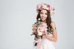 Γοητεία της χαμογελώντας νέας νύφης στο στεφάνι λουλουδιών με την όμορφη ανθοδέσμη στοκ εικόνες