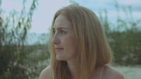 Γοητεία της redhead γυναίκας που πίνει το κρύο ποτό στην παραλία απόθεμα βίντεο
