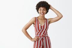 Γοητεία του θηλυκού και flirty πανέμορφου θηλυκού αφροαμερικάνων με το σγουρό hairstyle στο καθιερώνον τη μόδα ριγωτό κράτημα φορ στοκ φωτογραφία με δικαίωμα ελεύθερης χρήσης