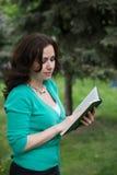 Γοητεία του μακρυμάλλους κοριτσιού με το βιβλίο στοκ εικόνα