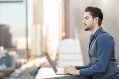 Γοητεία του νεαρού άνδρα που εργάζεται στο lap-top του στην πόλη Στοκ φωτογραφία με δικαίωμα ελεύθερης χρήσης