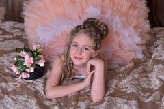Γοητεία του ξανθού κοριτσιού σε ένα άσπρο φόρεμα με ένα ροδάκινο Στοκ Εικόνα