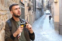 Γοητευμένο άτομο που κρατά μια εκλεκτής ποιότητας κάμερα κατά τη διάρκεια του ταξιδιού που φαίνεται ένα κάτι εντυπωσιακό στοκ φωτογραφία