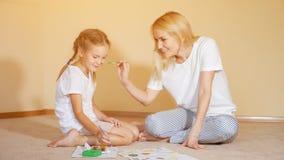 Γοητευτικά κορίτσια που κάθονται στο πάτωμα με τις μύτες εγγράφου και watercolor και ζωγραφικής ο ένας στον άλλο που έχουν τη δια στοκ φωτογραφίες