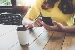 Γοητευτικά νέα χέρια κοριτσιών hipster που χρησιμοποιούν στην έξυπνη τηλεφωνική συνεδρίασή της στον ξύλινο πίνακα σε μια καφετερί Στοκ φωτογραφία με δικαίωμα ελεύθερης χρήσης