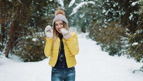 Γοητευτικά παιχνίδια κοριτσιών με τις χιονιές στη isthrowing χιονιά δασικών ενεργών νέων γυναικών στη κάμερα που έχει τη διασκέδα φιλμ μικρού μήκους