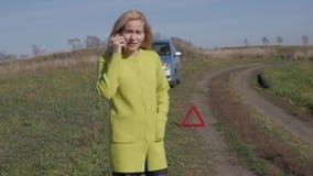 Γοητευτικές κλήσεις επιχειρησιακών γυναικών για τη βοήθεια με κινητό τηλέφωνο σπασμένο αυτοκίνητο κοριτσιών πλησίον στον αγροτικό φιλμ μικρού μήκους