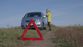 Γοητευτικές κλήσεις επιχειρησιακών γυναικών για τη βοήθεια με κινητό τηλέφωνο σπασμένο αυτοκίνητο κοριτσιών πλησίον στον αγροτικό απόθεμα βίντεο