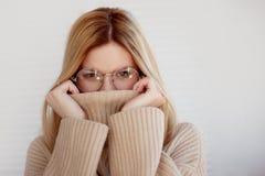 Γοητευτικές τη νέα γυναίκα σε ένα μαλακό πουλόβερ και τα γυαλιά, οι δορές αντιμετωπίζουν στο περιλαίμιο στοκ φωτογραφίες με δικαίωμα ελεύθερης χρήσης