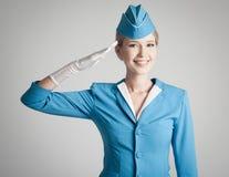 Γοητευτική αεροσυνοδός μπλε σε ομοιόμορφο στο γκρίζο υπόβαθρο στοκ φωτογραφία με δικαίωμα ελεύθερης χρήσης