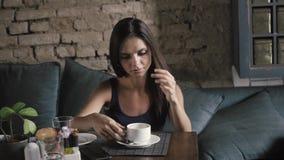 Γοητευτική γυναίκα με το όμορφο χαμόγελο που διαβάζει το κινητό τηλέφωνο κατά τη διάρκεια του υπολοίπου στη καφετερία, ευτυχές κα φιλμ μικρού μήκους