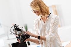 Γοητευτική γυναίκα που εξερευνά λίγο ρομπότ στο γραφείο Στοκ Εικόνες