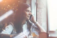 Γοητευτική γυναίκα που μιλά στο τηλέφωνο στον καφέ και που κοιτάζει στο παράθυρο Κέικ και καφές σοκολάτας στον πίνακα Στοκ Εικόνες