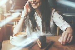 Γοητευτική γυναίκα που μιλά στο τηλέφωνο στον καφέ Νόστιμοι κέικ και καφές σοκολάτας στον πίνακα Φωτεινό ηλιόλουστο πρωί στον καφ Στοκ Φωτογραφίες