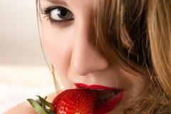 Γοητευτική γυναίκα που τρώει τη φράουλα στοκ φωτογραφίες με δικαίωμα ελεύθερης χρήσης