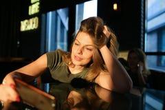 Γοητευτική γυναίκα χρησιμοποιώντας το smartphone και καθμένος στον καφέ στις ακτίνες ήλιων Στοκ Εικόνα