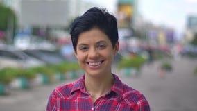 Γοητευτική γυναίκα brunette που χαμογελά στη κάμερα και που στέκεται στην οδό στην αστική πόλη, ευτυχής και εύθυμος φιλμ μικρού μήκους