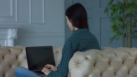 Γοητευτική δικτύωση γυναικών στο lap-top στο σπίτι απόθεμα βίντεο