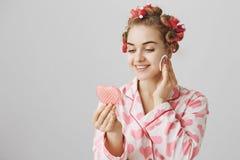 Γοητευτική ελκυστική γυναίκα με τα τρίχα-ρόλερ στο κεφάλι, που φορά τις πυτζάμες και που κρατά τον καρδιά-διαμορφωμένο καθρέφτη,  στοκ εικόνα