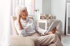 Γοητευτική ηλικιωμένη γυναικεία ανάγνωση από την ταμπλέτα προσεκτικά Στοκ εικόνα με δικαίωμα ελεύθερης χρήσης