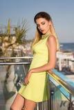 Γοητευτική και χαριτωμένη γυναίκα με τα μακριά ξανθά μαλλιά στο υπόβαθρο ενός ξενοδοχείου πολυτελείας Μια κυρία σε ένα φόρεμα με  στοκ εικόνα