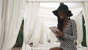 Γοητευτική κυρία αφροαμερικάνων σε ένα ριγωτά φόρεμα και ένα μαύρο καπέλο κοκτέιλ που χρησιμοποιούν την ταμπλέτα και το χαμόγελό