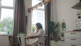 Γοητευτική νέα δακτυλογράφηση γυναικών στο φορητό προσωπικό υπολογιστή στο σπίτι απόθεμα βίντεο
