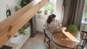 Γοητευτική νέα δακτυλογράφηση γυναικών στο φορητό προσωπικό υπολογιστή στο σπίτι φιλμ μικρού μήκους