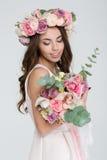 Γοητευτική νύφη στο στεφάνι των τριαντάφυλλων που εξετάζει την ανθοδέσμη λουλουδιών Στοκ Εικόνες