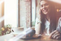 Γοητευτική ομιλία γυναικών χαμόγελου στο τηλέφωνο στον καφέ Κέικ και καφές σοκολάτας στον πίνακα Φωτεινό ηλιόλουστο πρωί στον καφ Στοκ Εικόνες