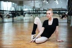 Γοητευτική συνεδρίαση ballerina στο πάτωμα Στοκ Εικόνες