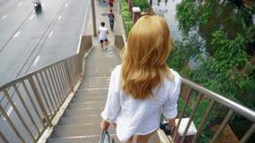 Γοητευτική τη νέα γυναίκα με τη χρυσή τρίχα, που περπατά στο κέντρο της πόλης, περπατά πέρα από τη γέφυρα στοκ εικόνες