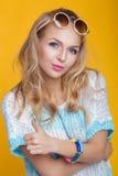 Γοητευτική όμορφη ξανθή γυναίκα στα γυαλιά ηλίου και το μπλε πουκάμισο που δίνουν τους αντίχειρες επάνω στο κίτρινο υπόβαθρο ευτυ Στοκ φωτογραφία με δικαίωμα ελεύθερης χρήσης