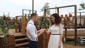 Γοητευτικός, ο νεόνυμφος φορά το γαμήλιο δαχτυλίδι στο δάχτυλο της νύφης του Έννοια: γάμος αγροτικός απόθεμα βίντεο