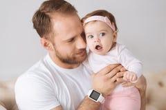 Γοητευτικός πατέρας που αγκαλιάζει την κόρη μικρών παιδιών του στο σπίτι Στοκ φωτογραφίες με δικαίωμα ελεύθερης χρήσης