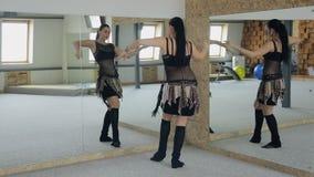 Γοητευτικός χορός κοιλιών πρακτικών brunette μπροστά από τον καθρέφτη απόθεμα βίντεο