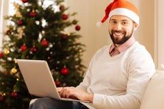 Γοητευτικό άτομο στην τοποθέτηση καπέλων Santa με το lap-top Στοκ φωτογραφία με δικαίωμα ελεύθερης χρήσης