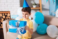Γοητευτικό αγόρι που εξετάζει το μπλε κιβώτιο με το παρόν γενεθλίων του στοκ εικόνες