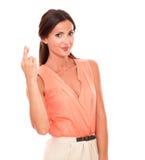 Γοητευτικό θηλυκό που διασχίζει τα δάχτυλα ως σημάδι τύχης Στοκ Εικόνα