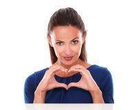 Γοητευτικό και προκλητικό θηλυκό που κάνει ένα σημάδι αγάπης Στοκ εικόνα με δικαίωμα ελεύθερης χρήσης
