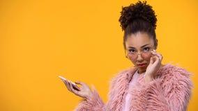 Γοητευτικό κομψό θηλυκό με διαθέσιμο να φανεί smartphone ενοχλημένη κάμερα στοκ φωτογραφίες