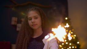 Γοητευτικό κορίτσι με τα Χριστούγεννα εορτασμού sparkler φιλμ μικρού μήκους