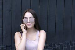 Γοητευτικό κορίτσι με την καθιερώνουσα τη μόδα συσκευή που απολαμβάνει τη συνομιλία στοκ εικόνες