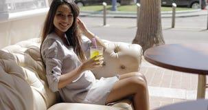 Γοητευτικό κορίτσι που έχει το αναζωογονώντας ποτό στον καφέ απόθεμα βίντεο