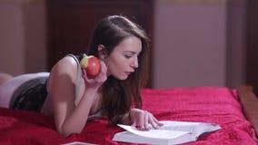 Γοητευτικό κορίτσι που διαβάζει ένα βιβλίο στο σπίτι απόθεμα βίντεο