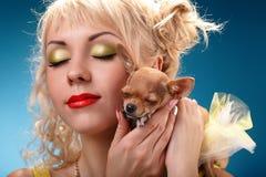 Γοητευτικό κορίτσι που κρατά ένα σκυλί chihuahua Ξανθός αγκαλιάζοντας ένα κουτάβι Στοκ Εικόνα