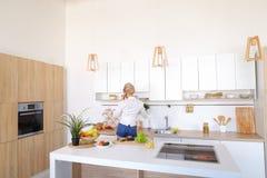 Γοητευτικό κορίτσι που μιλά στο τηλέφωνο και την προετοιμασία του γεύματος στο μοντέρνο Κ Στοκ Φωτογραφία