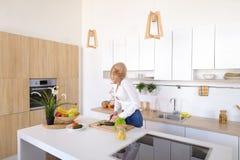 Γοητευτικό κορίτσι που μιλά στο τηλέφωνο και την προετοιμασία του γεύματος στο μοντέρνο Κ Στοκ φωτογραφία με δικαίωμα ελεύθερης χρήσης