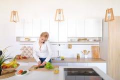 Γοητευτικό κορίτσι που μιλά στο τηλέφωνο και την προετοιμασία του γεύματος στο μοντέρνο Κ Στοκ Εικόνες