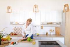 Γοητευτικό κορίτσι που μιλά στο τηλέφωνο και την προετοιμασία του γεύματος στο μοντέρνο Κ Στοκ εικόνα με δικαίωμα ελεύθερης χρήσης